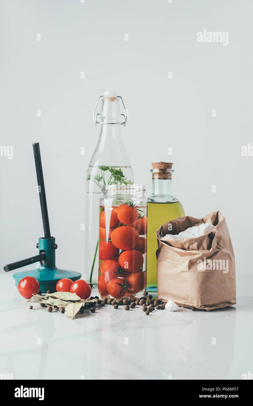 ingredients for preparing preserved tomatoes on kitchen table - Stock Image