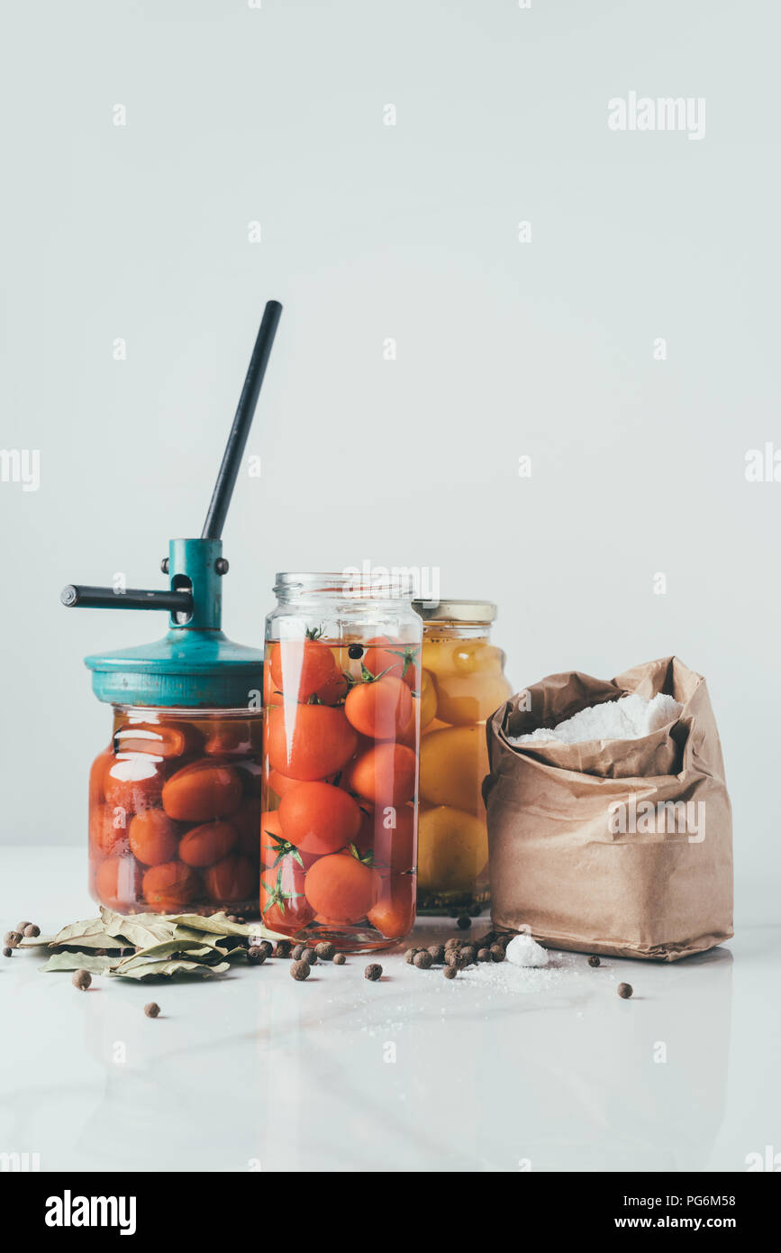 glass jars and tool for preserving tomatoes on table in kitchen - Stock Image