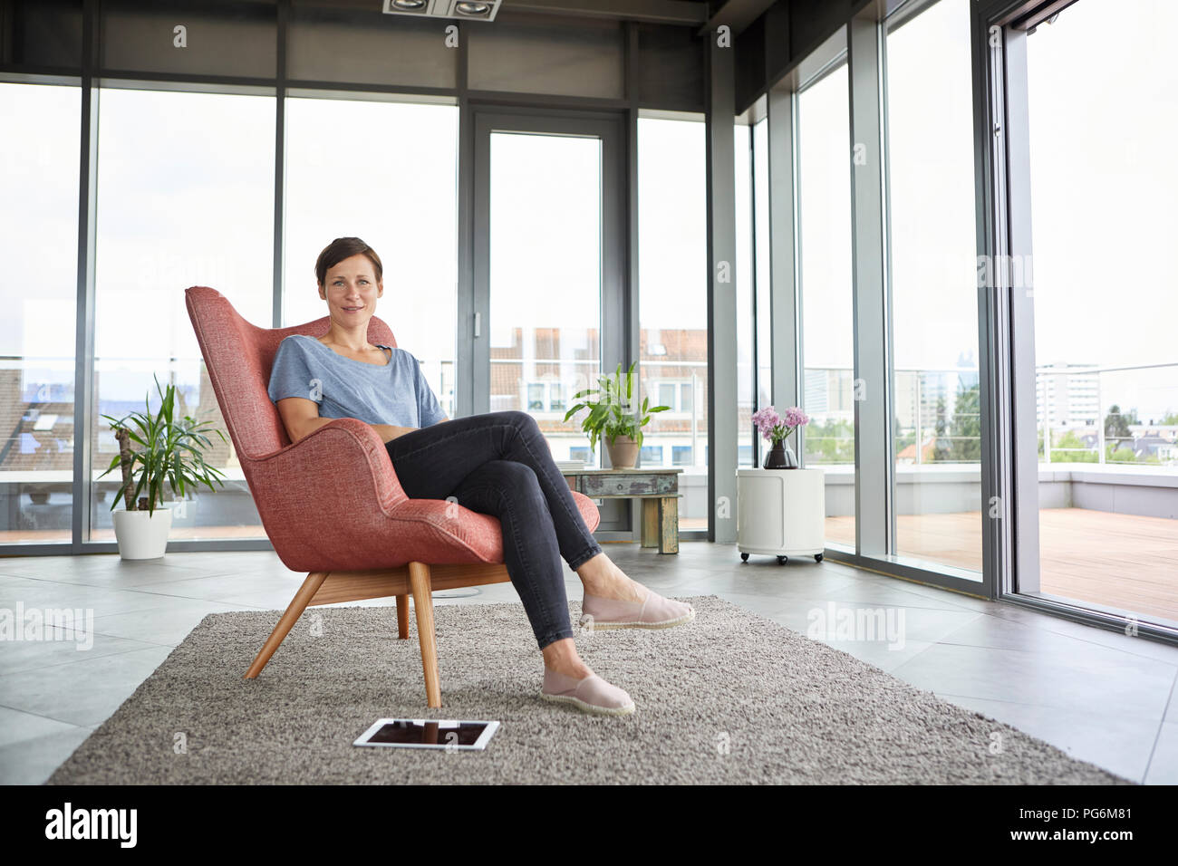 Portrait of woman sitting in armchair at home with tablet beside her - Stock Image