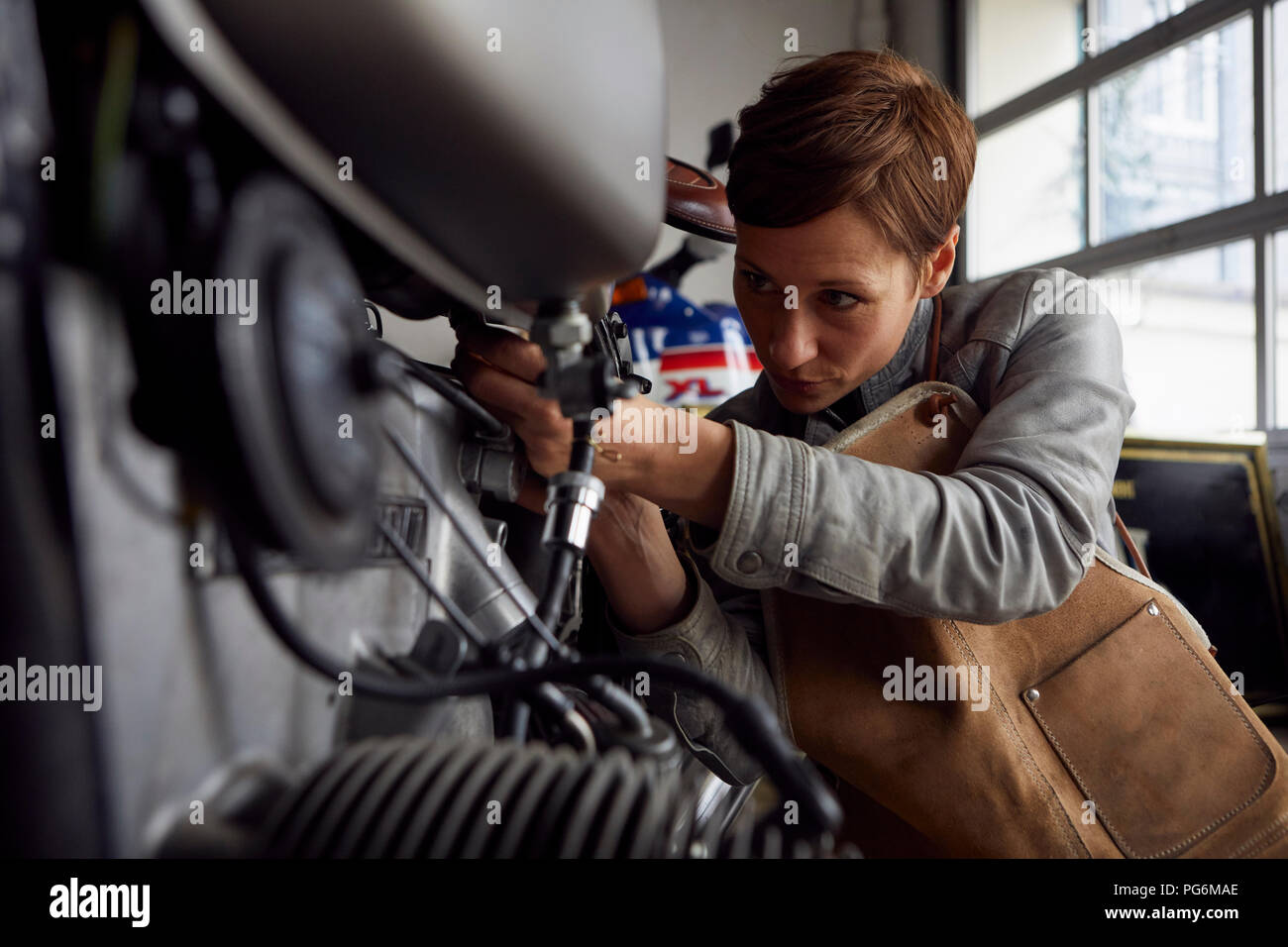 Woman working in repair workshop - Stock Image