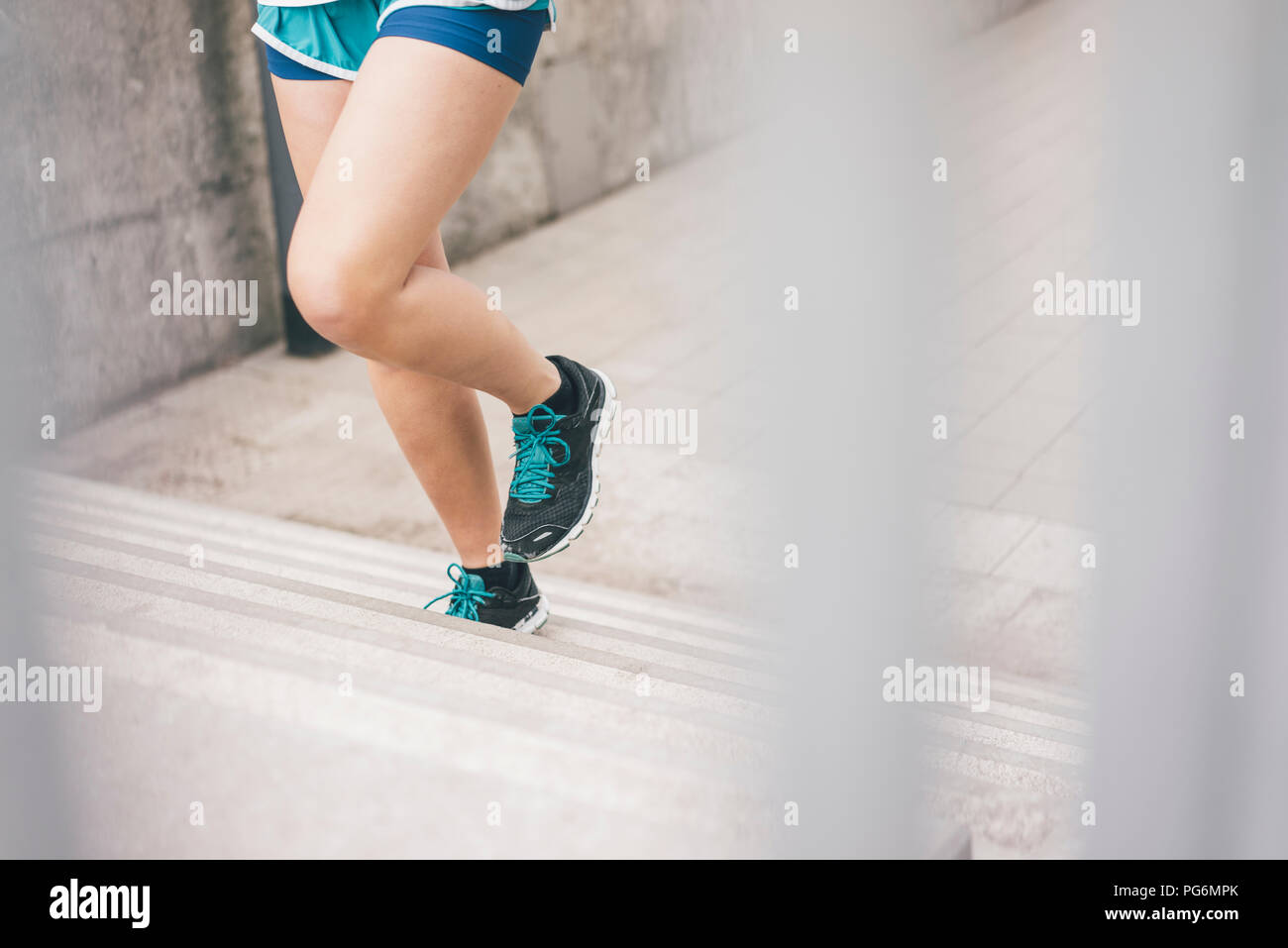 Close-up of woman running upstairs - Stock Image