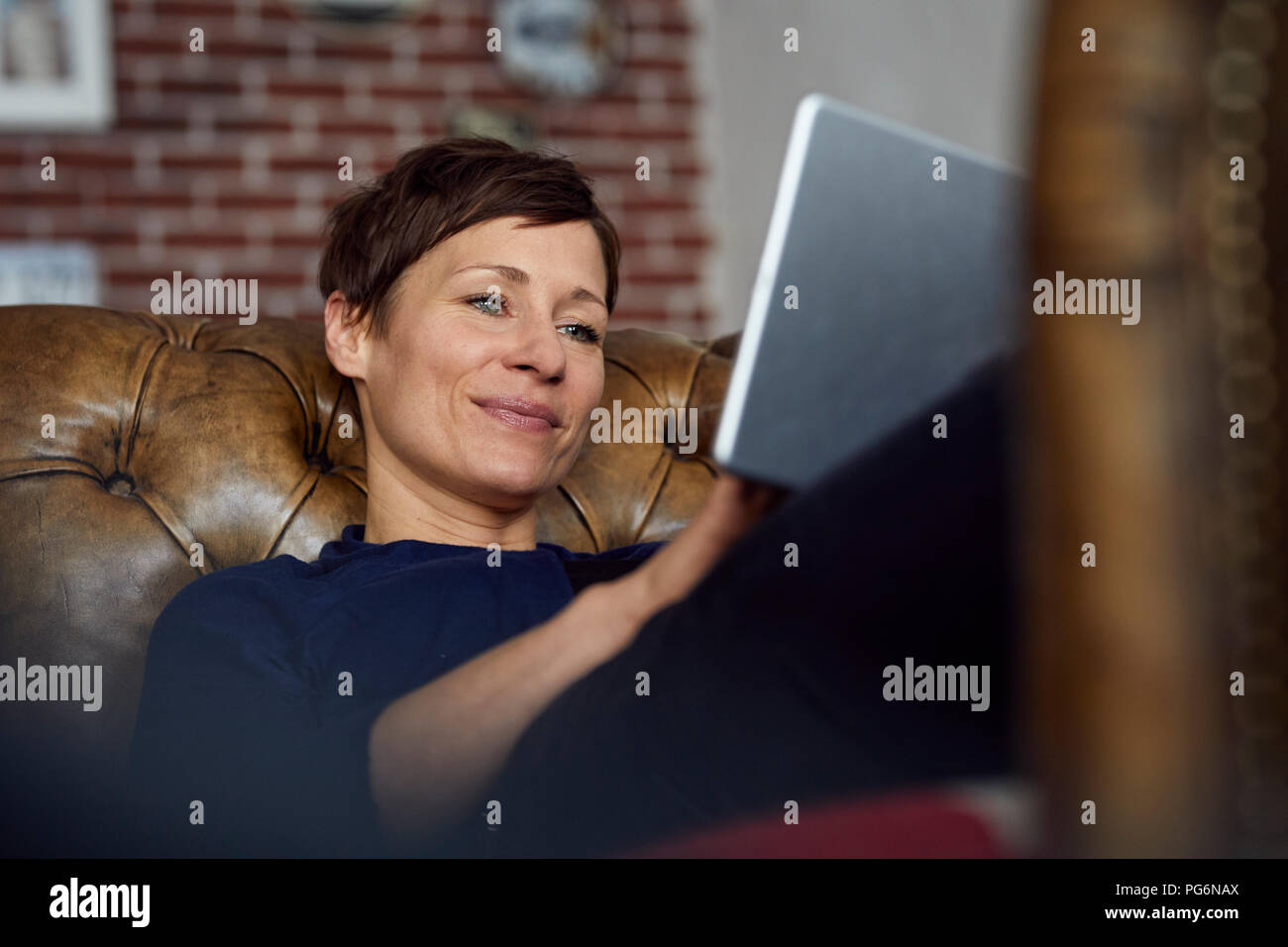 Woamn sitting on sofa at home, using digital tablet - Stock Image