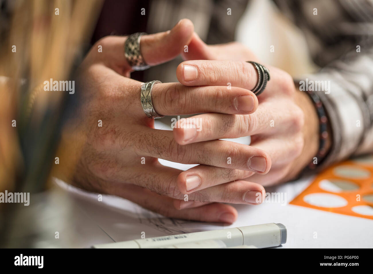 Close-up of artist's hands resting on table - Stock Image