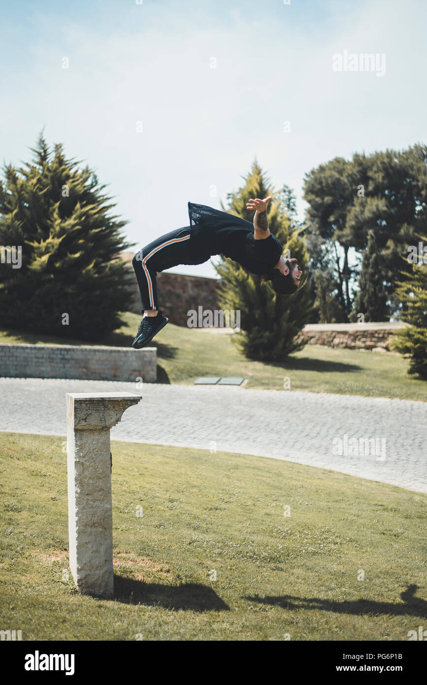 Tattooed man doing parkour in a park - Stock Image