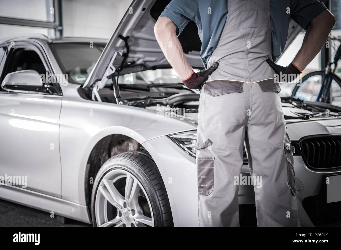 Modern Car Warranty Recall Fix. Mechanic in Front of the Vehicle in the Authorized Service Center. - Stock Image