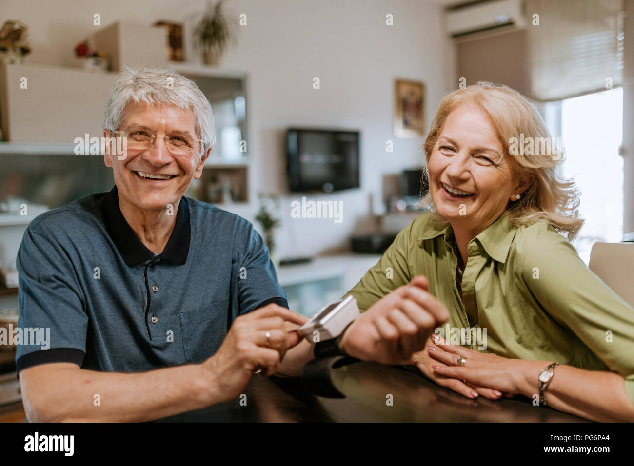 Smiling senior couple with blood pressure gauge - Stock Image