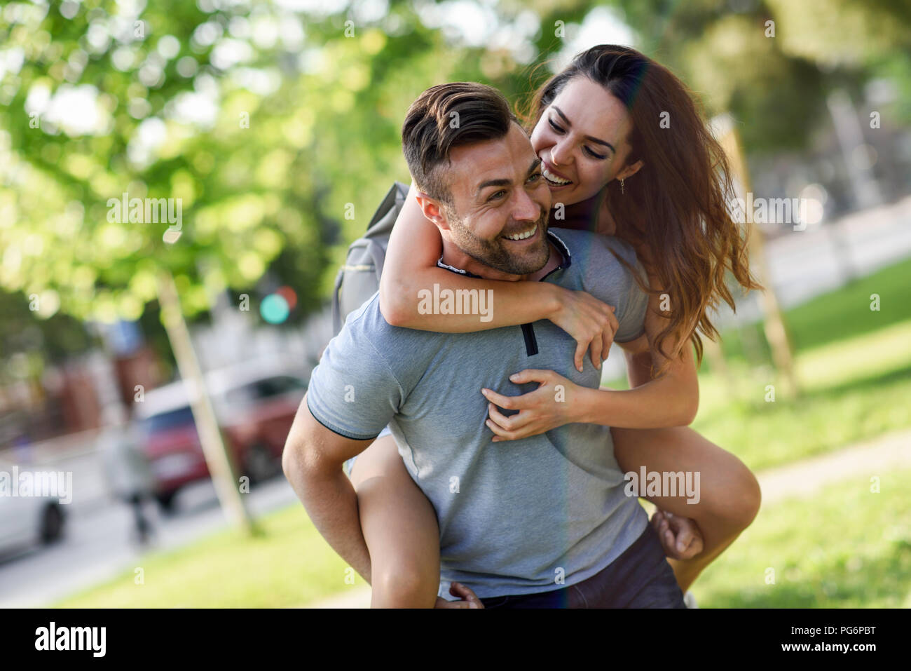 Happy man giving girlfriend a piggyback ride in park - Stock Image