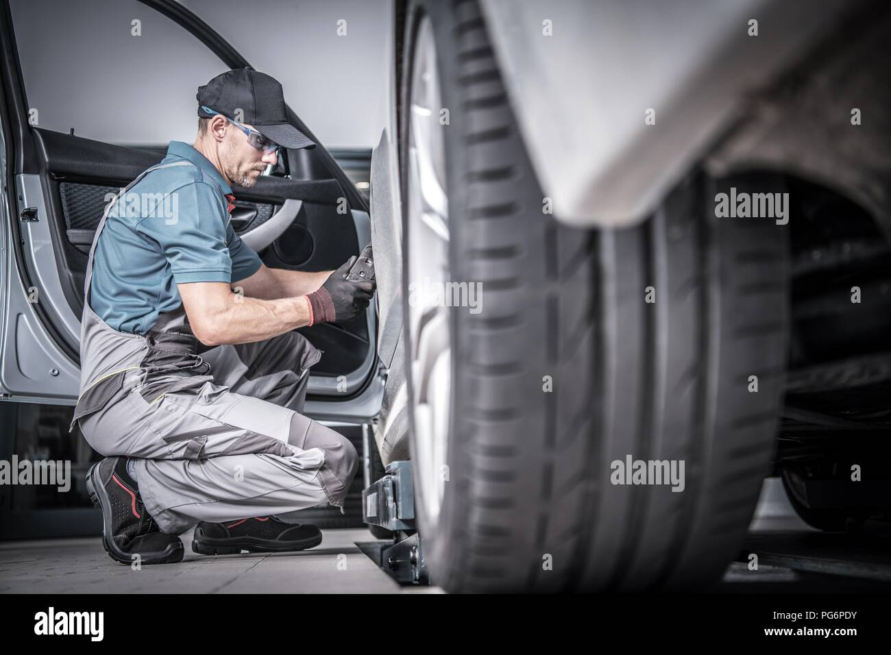 Used Car Under Maintenance. Caucasian Car Mechanic Looking For Potential Problems Inside the Vehicle. - Stock Image