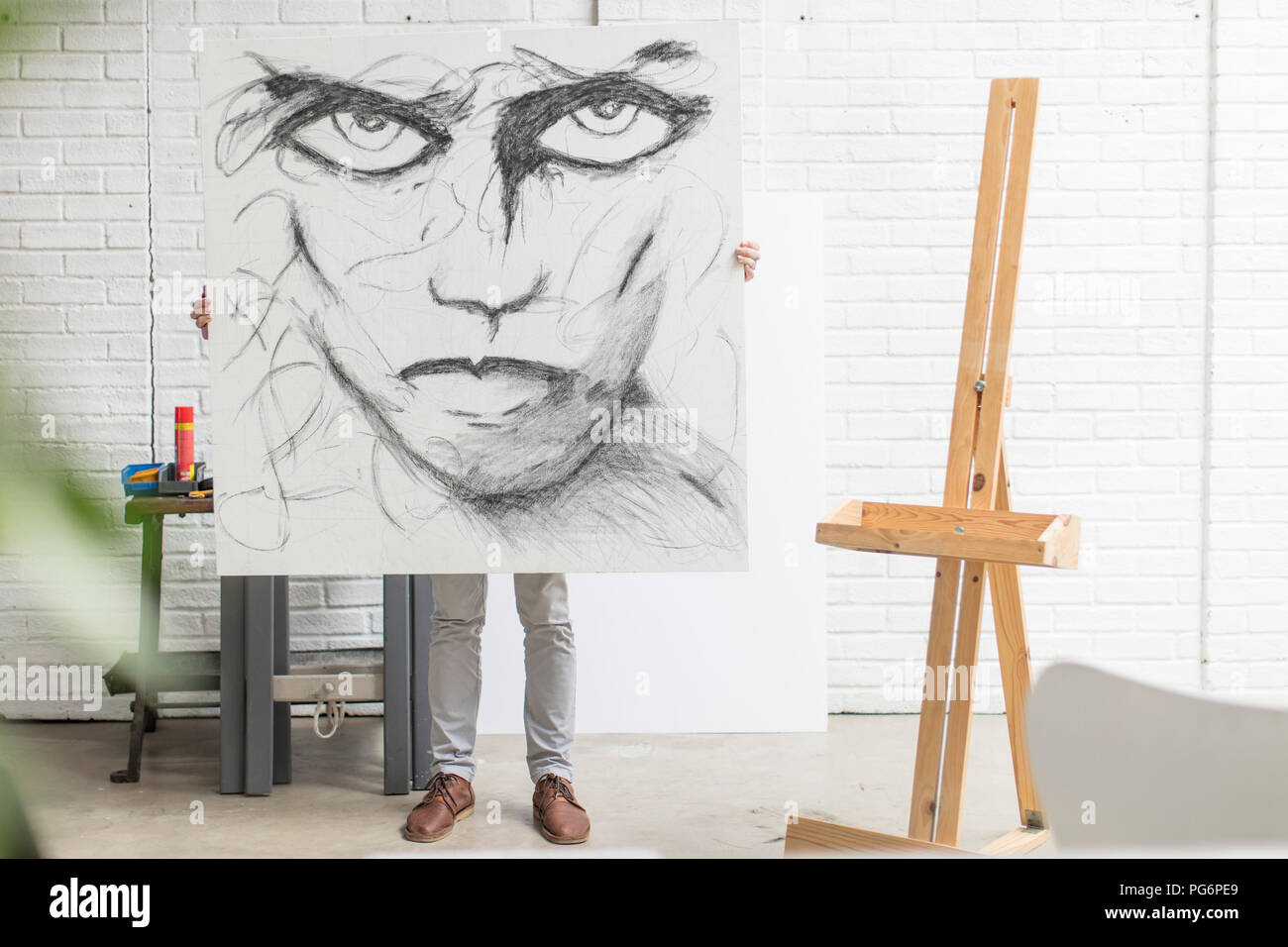 Obscured artist behind canvas holding drawing in studio - Stock Image