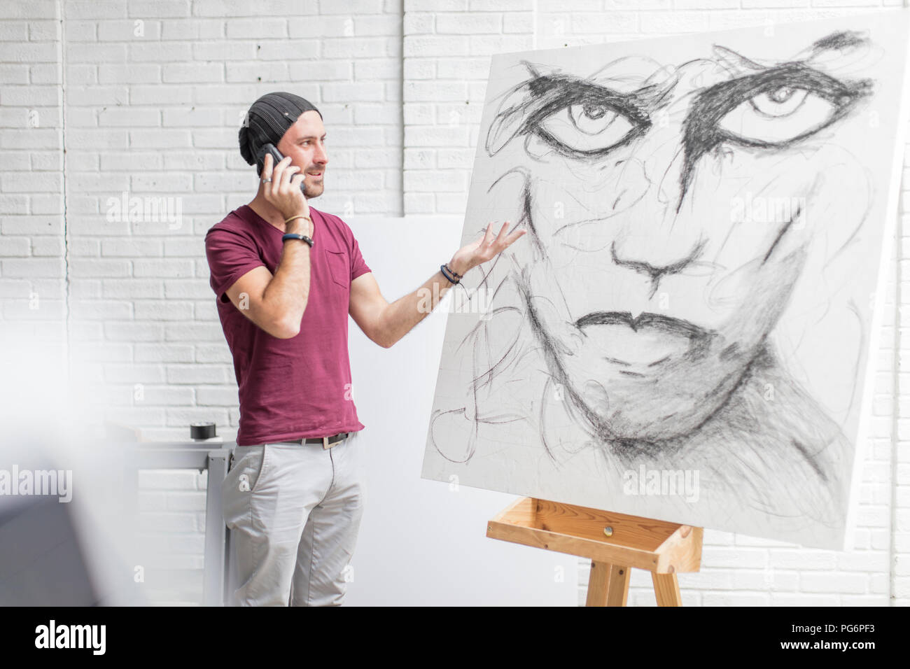Artist on the phone in studio next to drawing - Stock Image