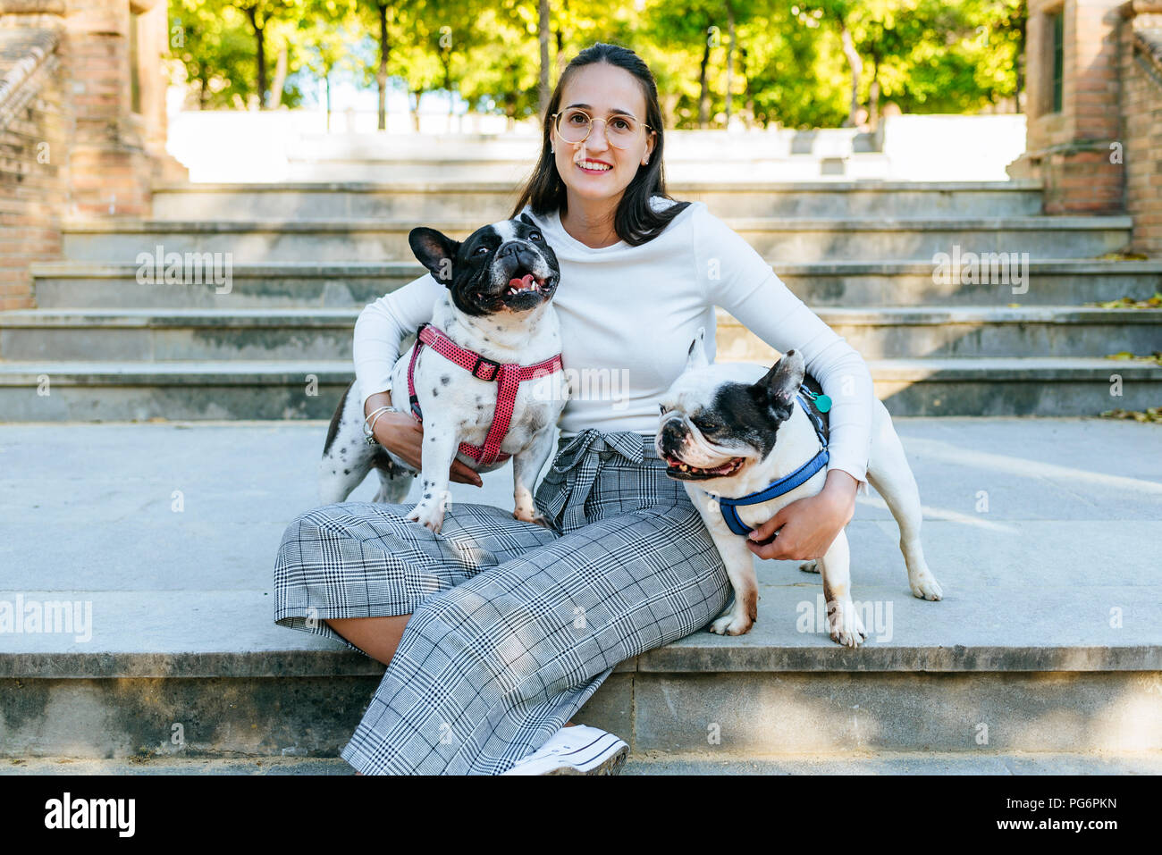 Portrait of woman sitting in the park with her two dogs - Stock Image