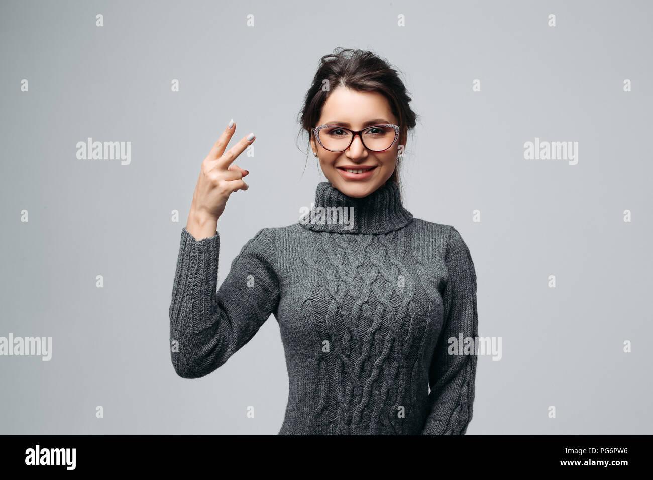 Joyous girl in glasses demonstrating victory sign - Stock Image