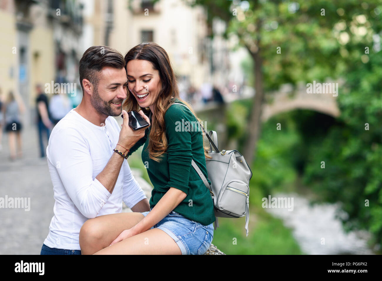 Happy tourist couple using cell phone in the city Stock Photo