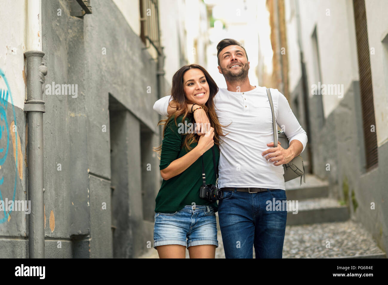 Happy tourist couple walking in the city - Stock Image