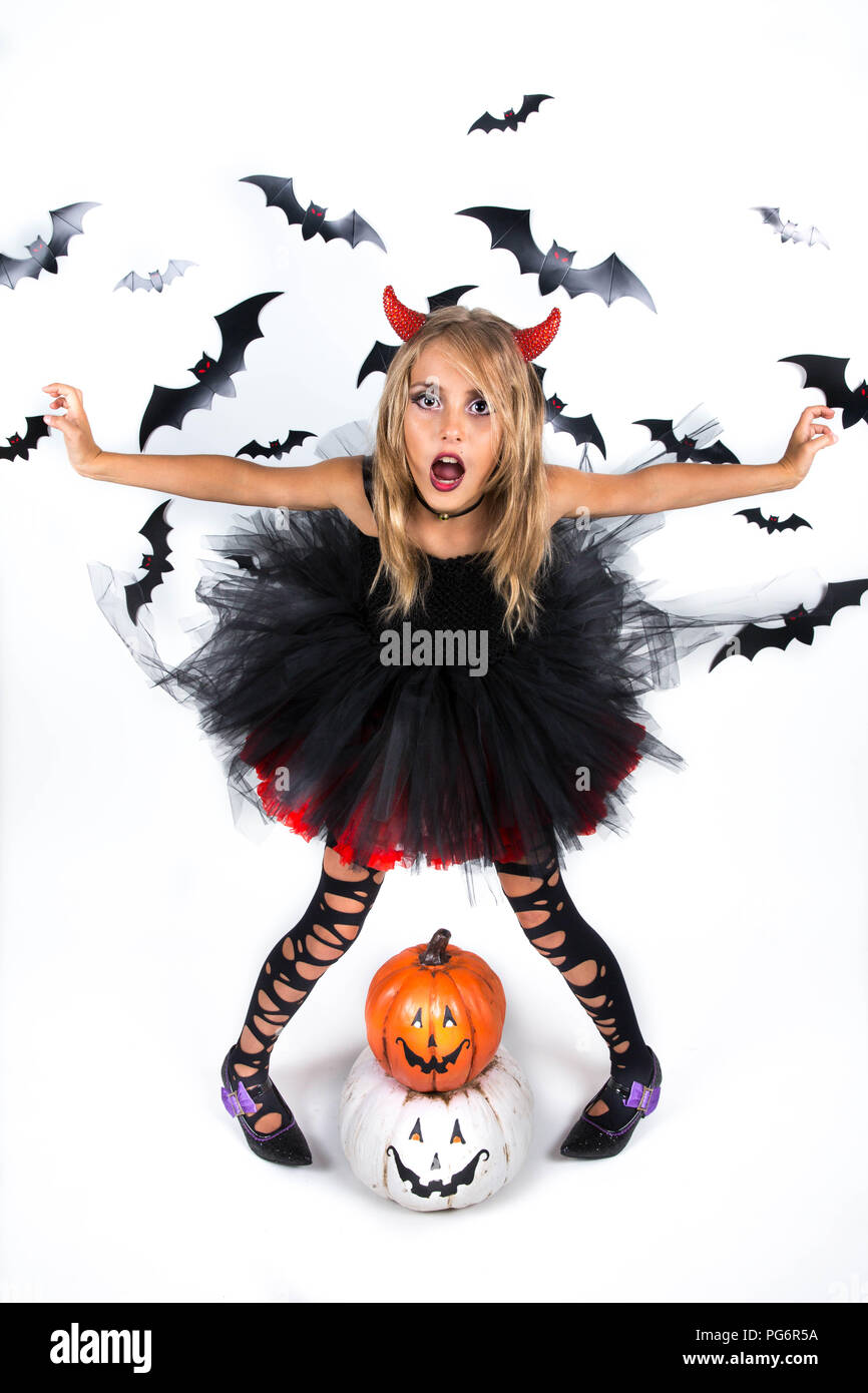 Little Girl with a demon devil costume dressed up in black red dress and red devil horns  for pumpkin patch and halloween party, posing with happy smi - Stock Image