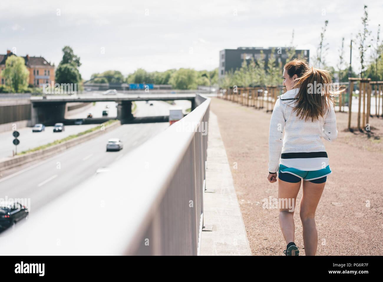 Sportive young woman walking beside motorway - Stock Image