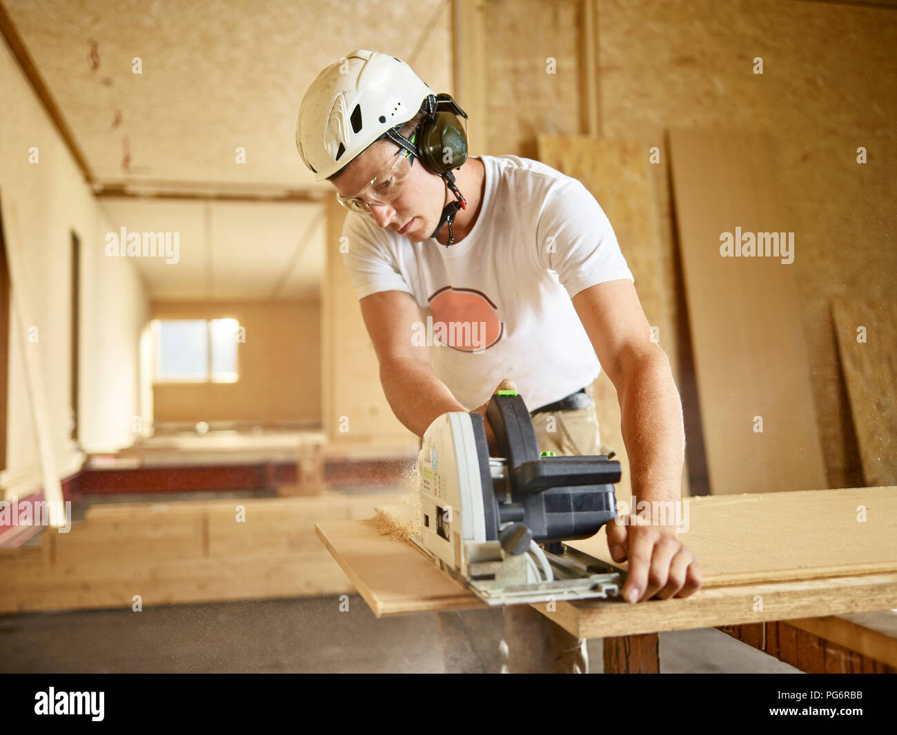 Worker with helmet sawing wood with circular saw - Stock Image