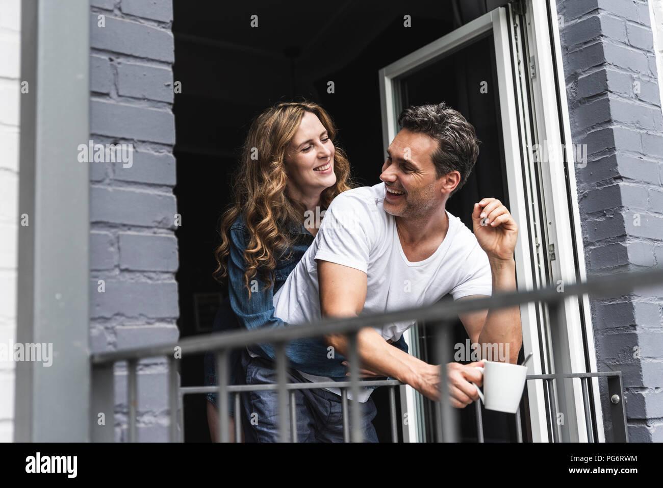 Happy couple in nightwear at home at balcony door - Stock Image
