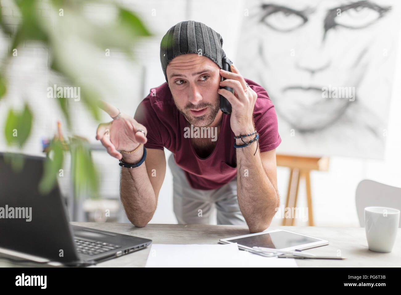 Artist on cell phone in studio - Stock Image
