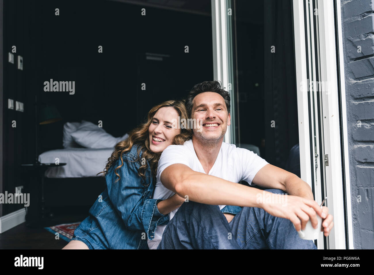 Happy couple in nightwear at home sitting at French window - Stock Image