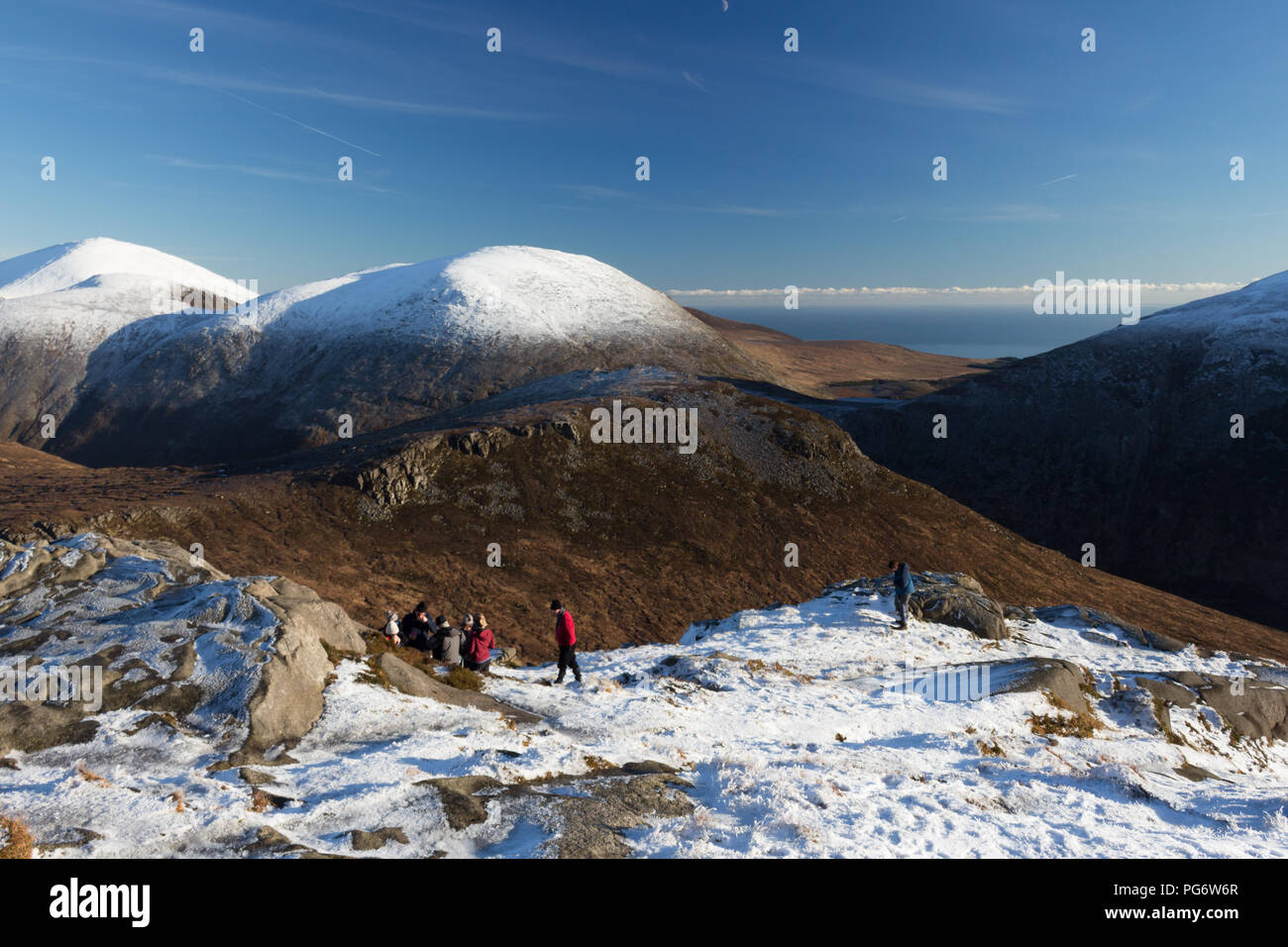 Group of winter hillwalkers enjoying a rest on Doan mountain. Views to Ben Crom directly in front and snowcapped Lamagan behind. Slieve Donard on left. - Stock Image