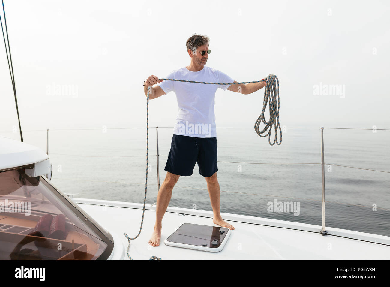 Mature man standing on catamaran, coiling rope - Stock Image