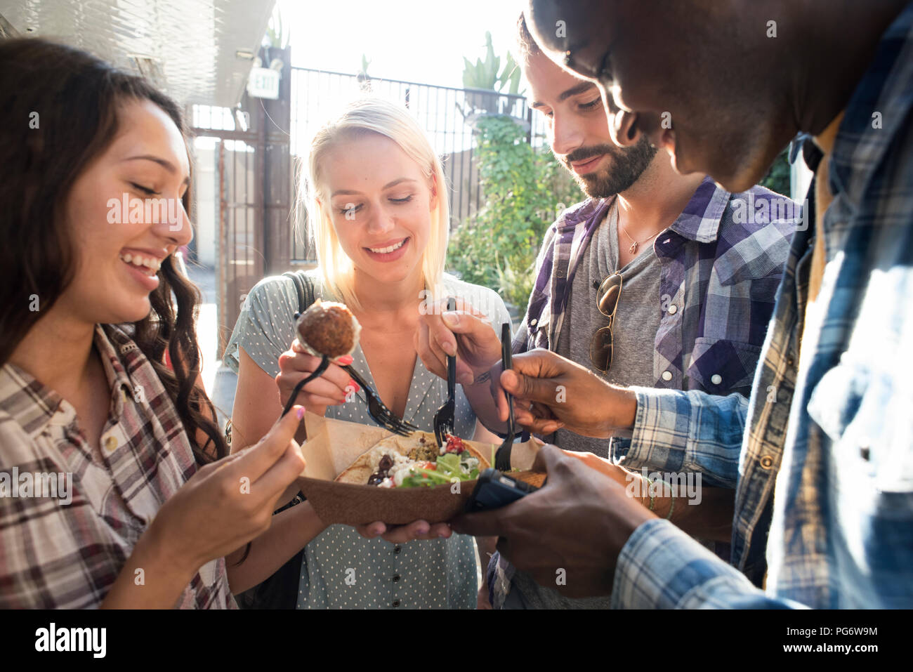 Happy friends sharing takeaway food outdoors Stock Photo