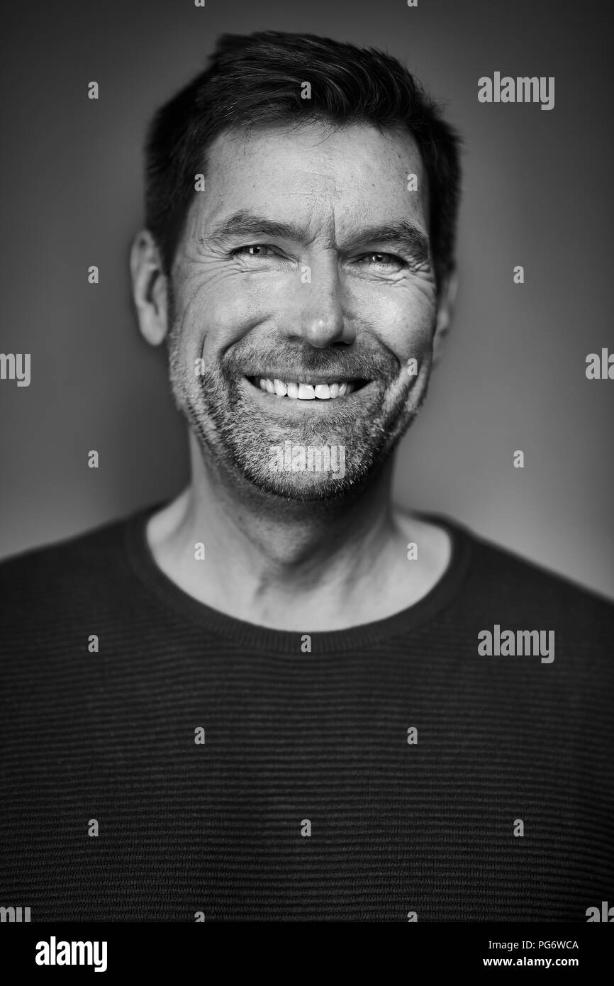 Portrait of smiling man, black and white - Stock Image