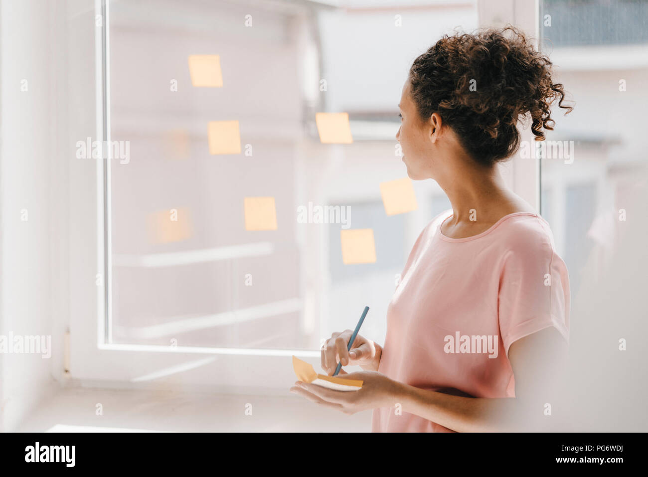 Woman posting adhesive notes on window, brainstorming - Stock Image