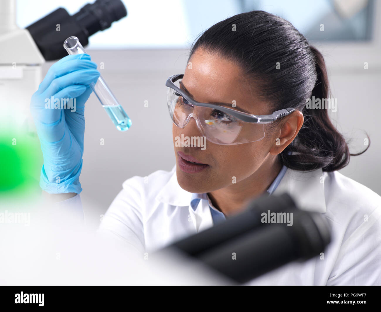 Biotechnology Research, female scientist mixing a chemical formula - Stock Image