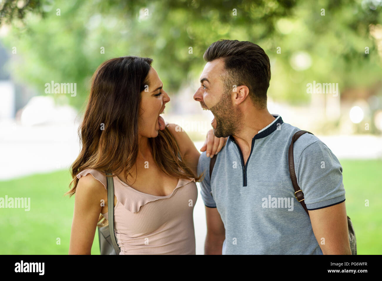 Couple looking at each other pulling funny faces - Stock Image
