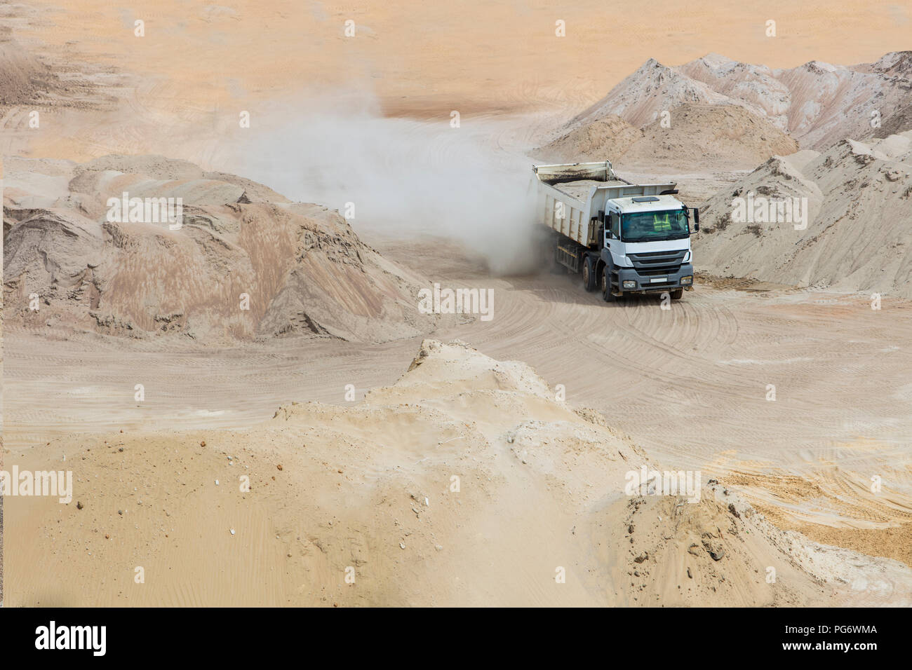 Truck driving through sand heaps Stock Photo