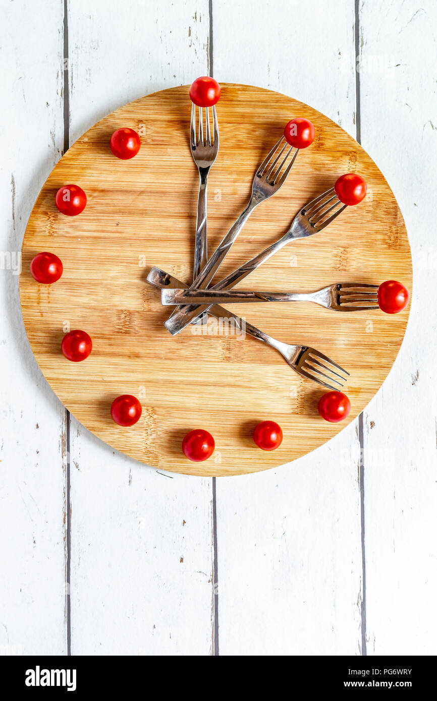 Vegetables on round chopping board, symbol for intermittent  fasting Stock Photo