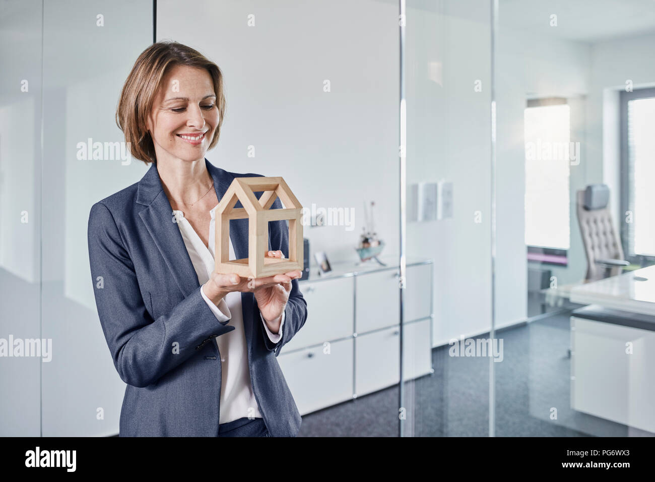 Smiling businesswoman looking at architectural model in office - Stock Image