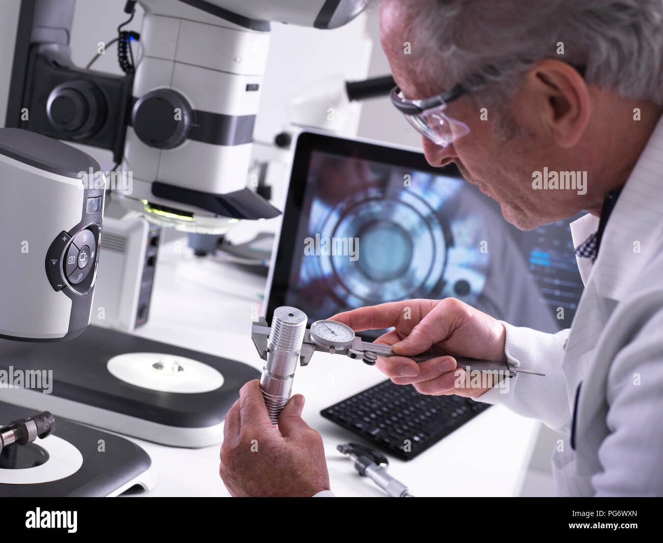 Engineer using a dial calliper and a 3d stereo microscope for quality control in the manufacturing of engineering components for industry - Stock Image