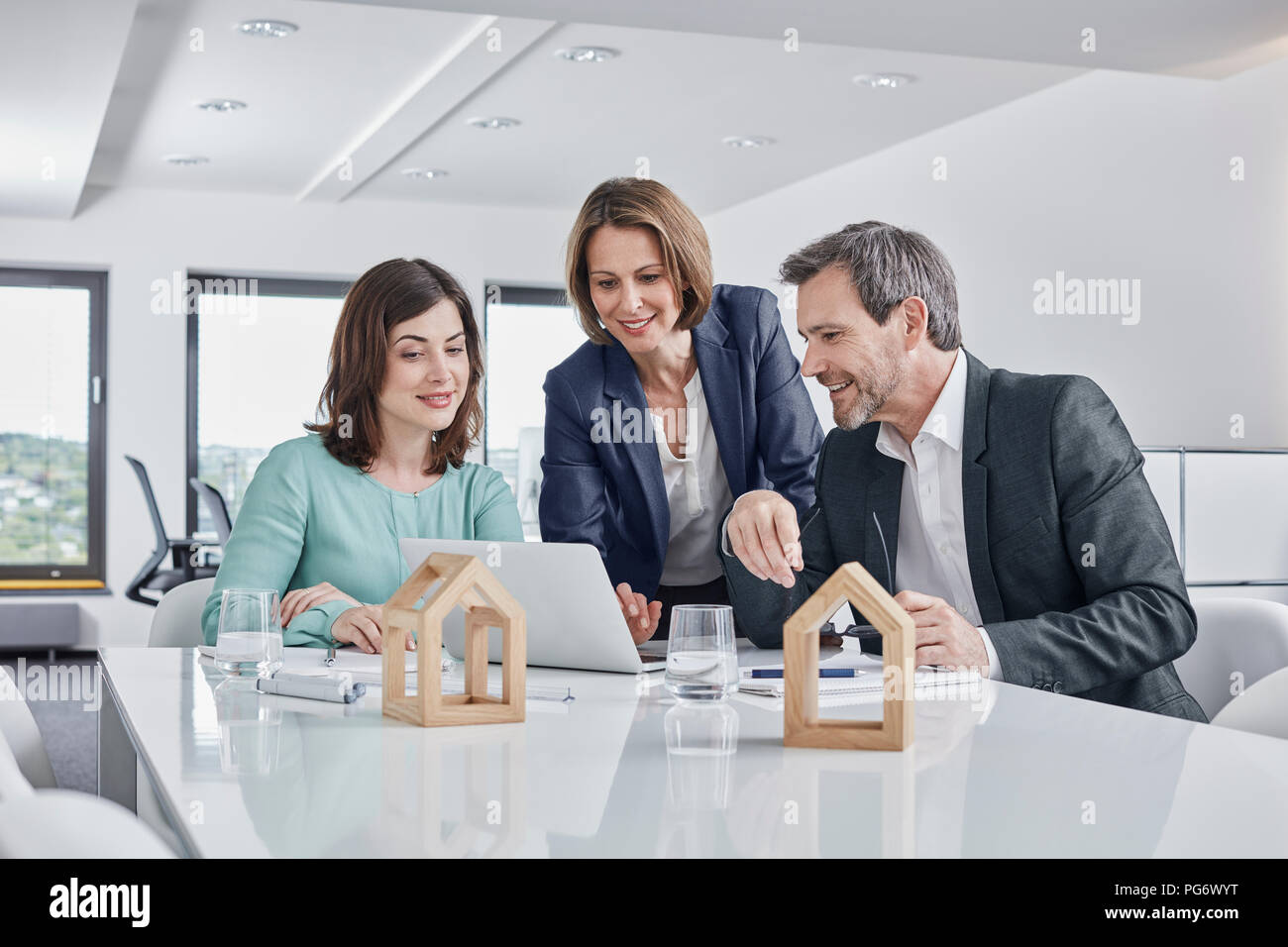 Business people having a meeting in office with laptop and architectural models - Stock Image