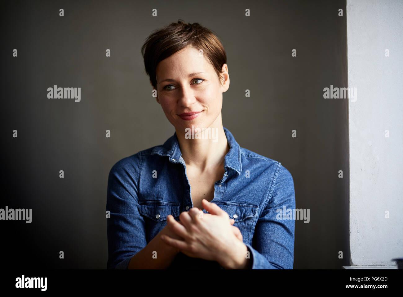 Portrait of ana ttractive woman, wearing denim shirt - Stock Image