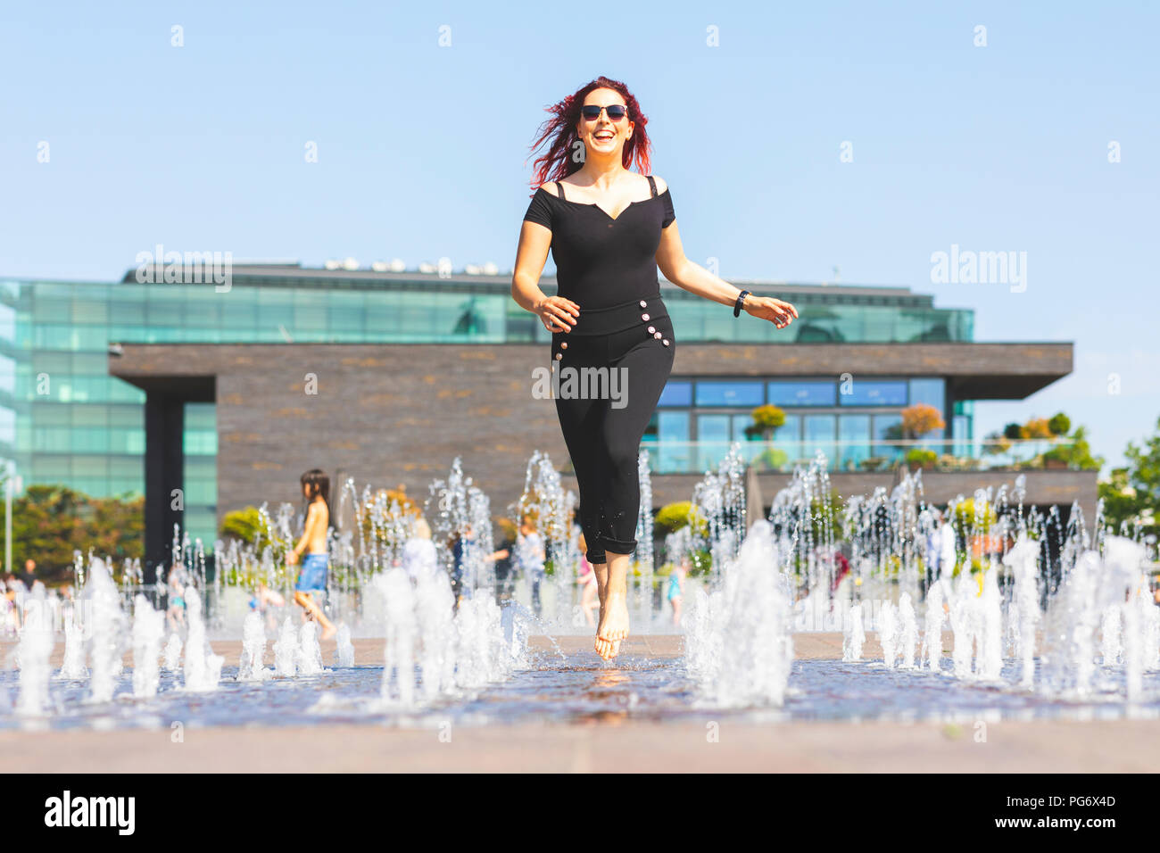 Young woman having fun running through a fountain - Stock Image