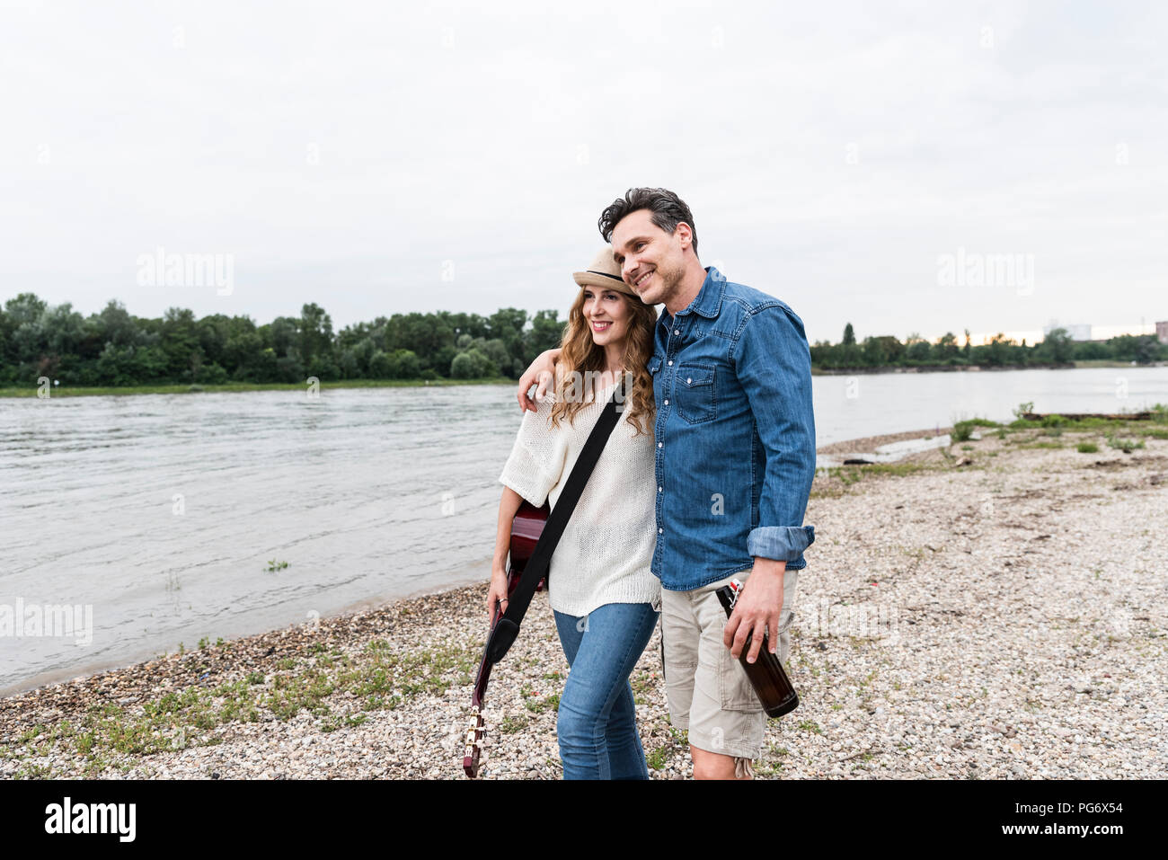 Happy couple walking at the riverside with beer bottle and guitar - Stock Image