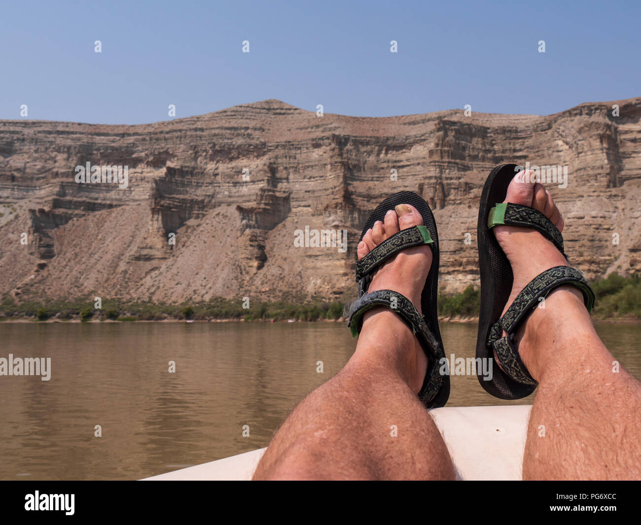 Feet and Tevas, lazy day in upper Desolation Canyon north of Green River, Utah. - Stock Image