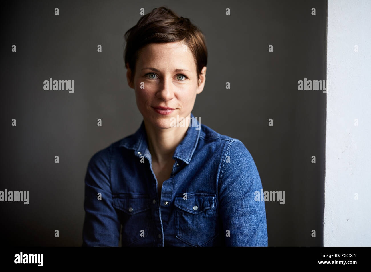 Portrait of ana ttractive woman, wearing denim shirt - Stock Image