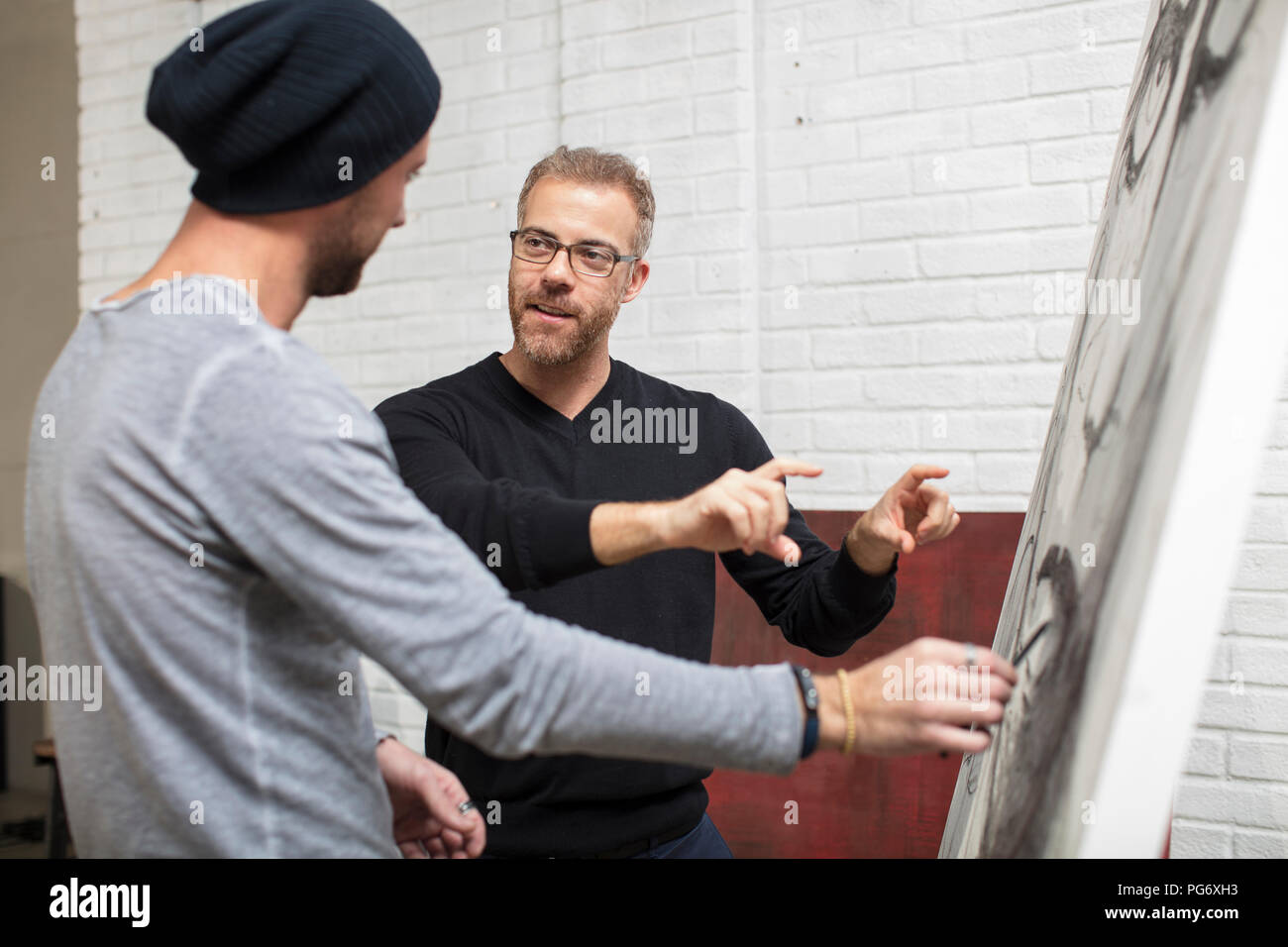 Artist discussing drawing with man in studio - Stock Image