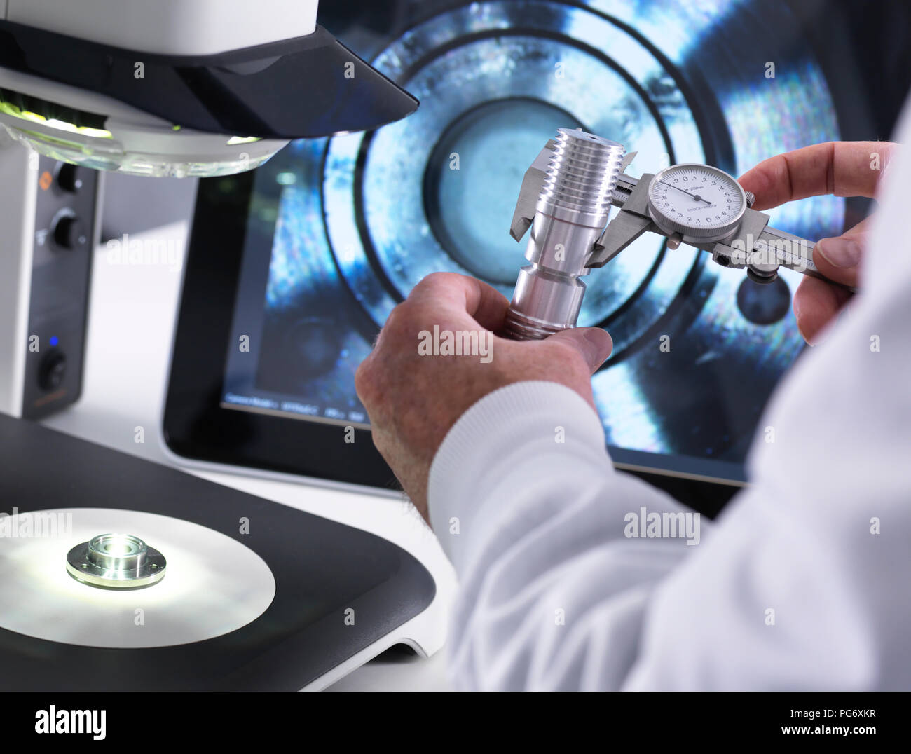 Engineer using a calliper and a 3d stereo microscope for quality control in the manufacturing of engineering components for industry - Stock Image