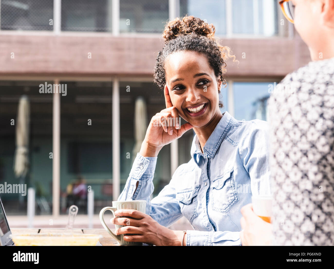Young colleagues sitting outdoors, working together, having lunch - Stock Image