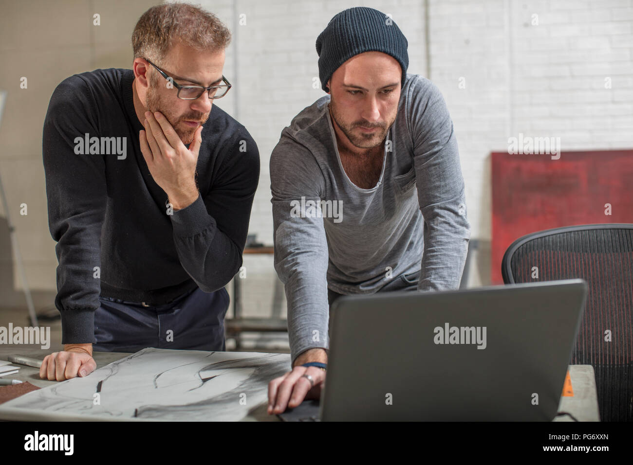 Artist using laptop with man in studio - Stock Image