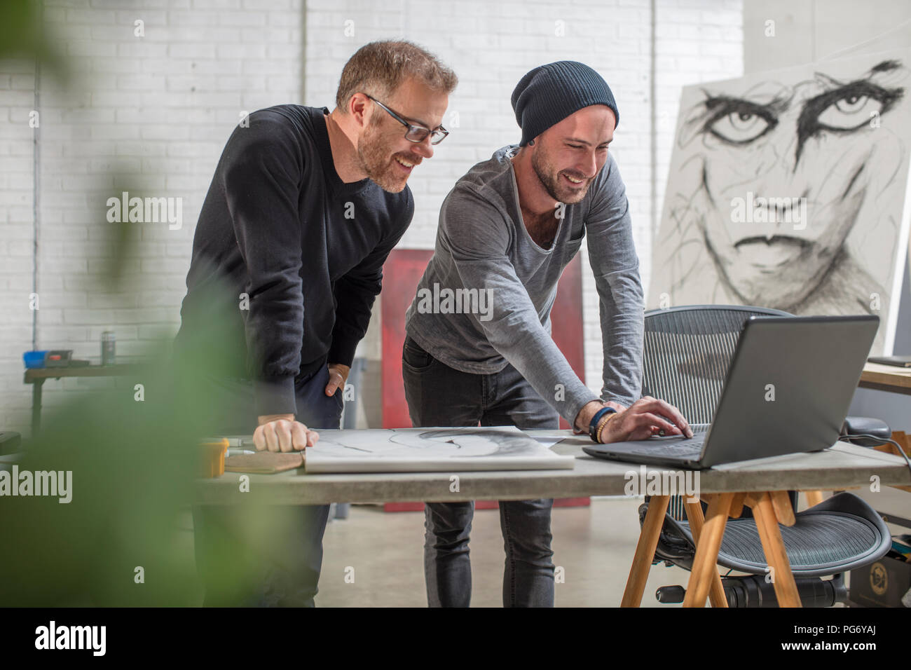 Smiling artist using laptop with man in studio - Stock Image