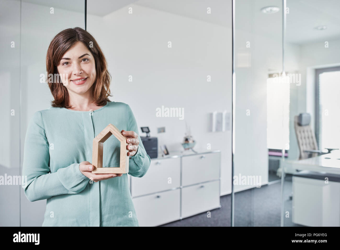Portrait of smiling young businesswoman holding architectural model in office - Stock Image