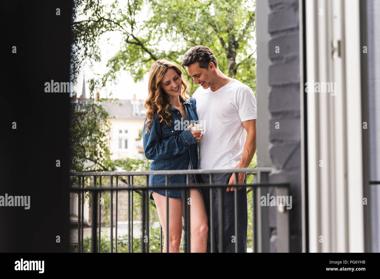 Smiling couple in nightwear with cup of coffee standing on balcony - Stock Image