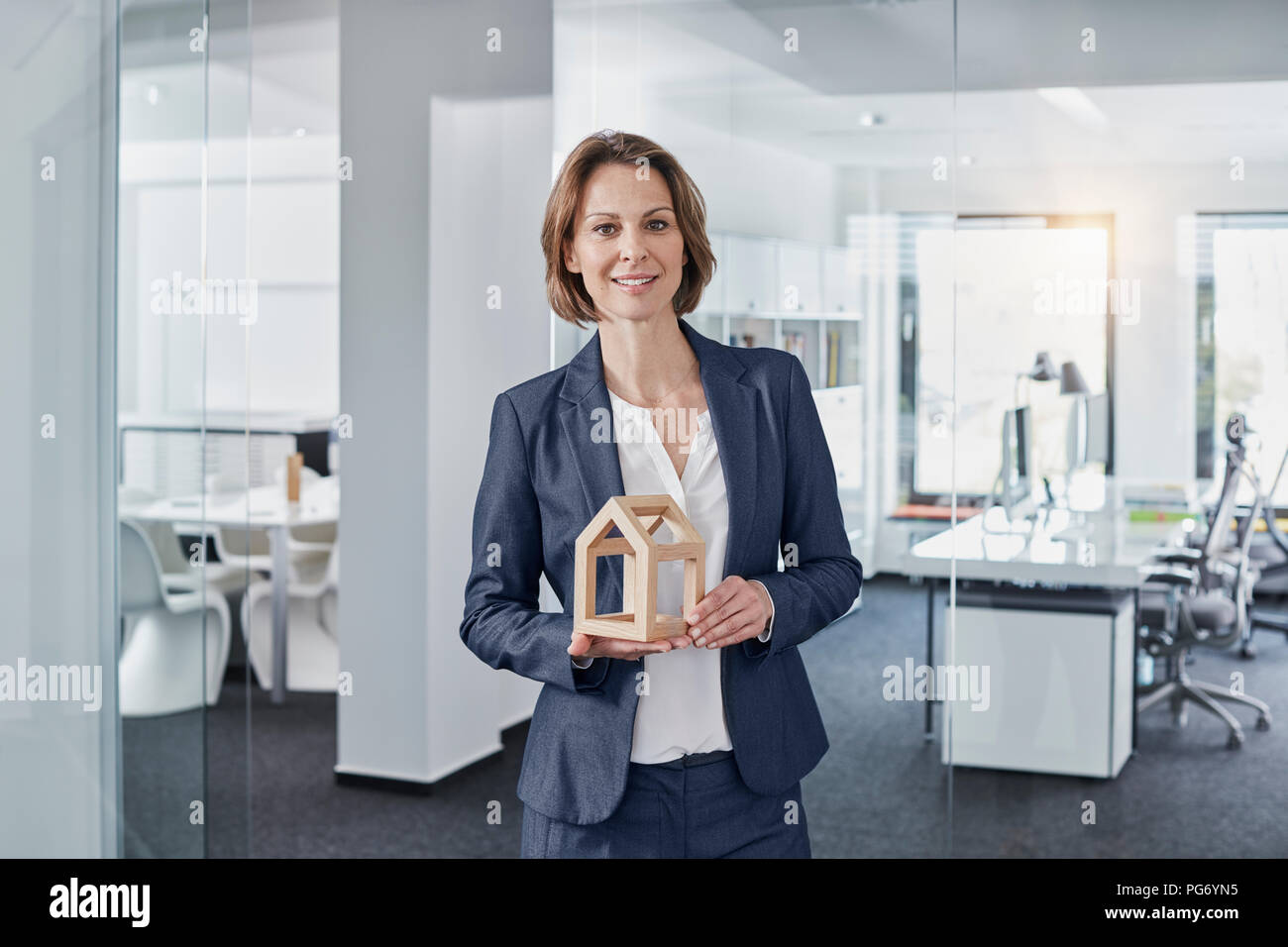 Portrait of smiling businesswoman holding architectural model in office - Stock Image