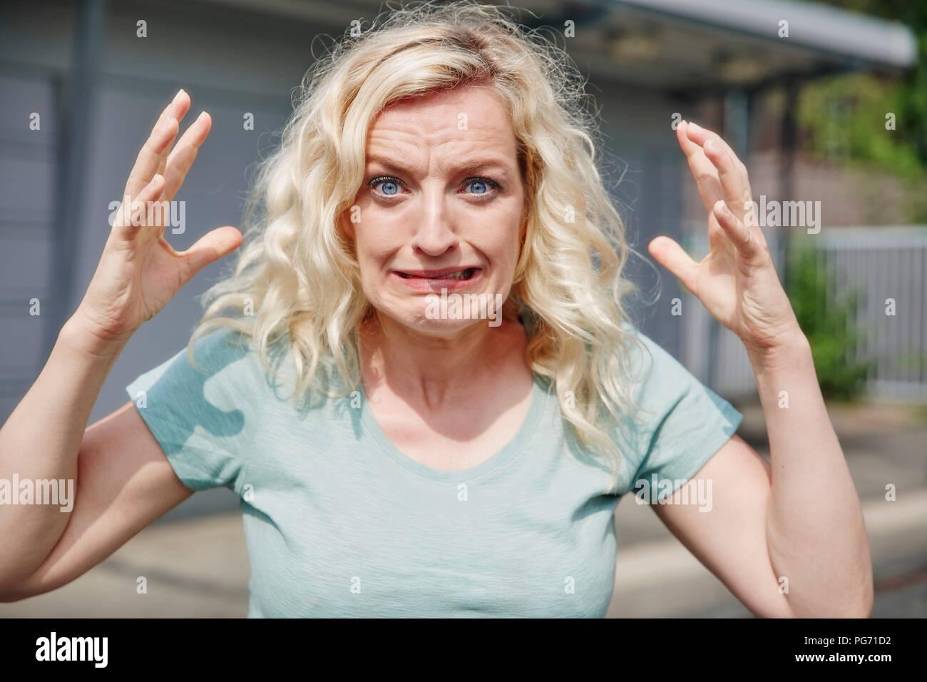 Portrait of grimacing woman outdoors - Stock Image